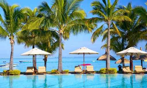 Swimming pool with  umbrellas on beach in Mauritius